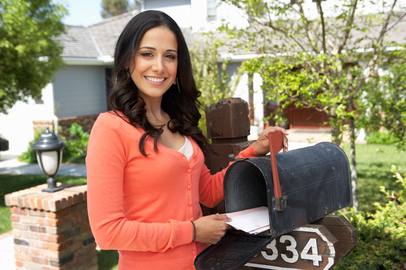 woman receiving direct local mail at mailbox
